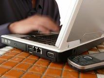 生意人移动电话笔记本键入 库存图片