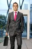生意人给正式年轻人穿衣 免版税库存图片