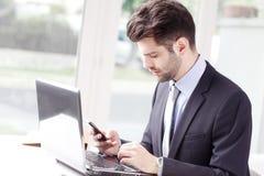 生意人膝上型计算机运作的年轻人 库存照片
