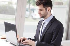 生意人膝上型计算机运作的年轻人 免版税库存照片