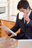 生意人饮用的咖啡的纵向,当读新闻时 免版税库存照片