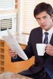 生意人饮用的茶的纵向,当读报纸时 库存照片