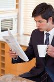 生意人饮用的茶的纵向,当读新闻时 免版税图库摄影