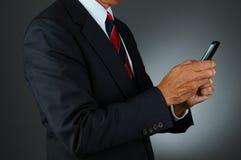 生意人Texting用两个现有量 免版税库存图片
