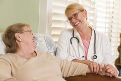 医生或护士谈话与坐资深妇女 库存图片