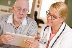 医生或护士谈话与有触摸板的老人 免版税库存图片