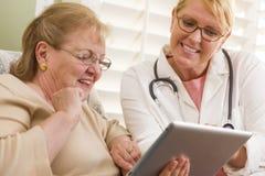 医生或护士谈话与有触摸板的资深妇女 库存图片
