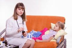 医生打开小女孩的医学瓶 库存照片