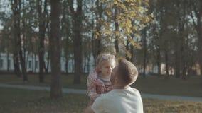 生投掷和抓住他的女儿在休闲公园在日落 股票录像