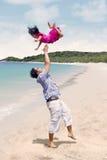 生投掷女儿在天空中在海滩 库存图片