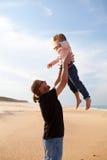 生投掷的女儿在天空中在海滩 库存图片