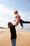 生投掷的女儿在天空中在海滩 图库摄影