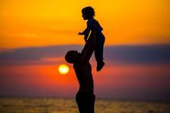 生投掷他的孩子悬而未决在海滩,剪影射击 免版税库存照片