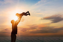 生投掷他的海滩的儿子在日落时间 概念 库存图片