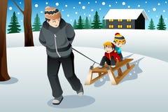 生拉扯他的乘坐在雪撬的儿子 免版税库存照片