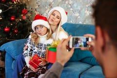 生拍他滑稽的妻子和女儿照片圣诞老人`的s ha 免版税图库摄影