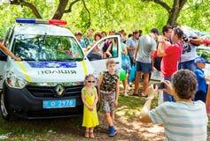 生拍他的孩子照片在新的乌克兰警车附近 免版税库存图片