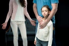 生拥抱有母亲的女儿后边黑色的 免版税库存照片