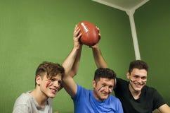 生拿着与他的儿子的橄榄球球,复制空间 免版税图库摄影