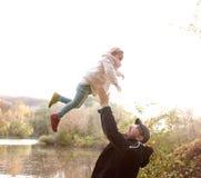 生拿着小女儿,投掷她在天空中 免版税库存照片