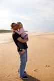 生拿着胳膊的女儿在海滩 免版税库存图片