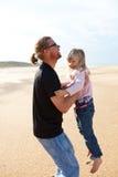 生拿着胳膊的女儿在海滩 库存照片