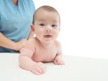 医生按摩小白种人婴孩 免版税库存照片