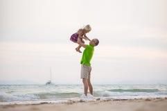 生提起在手上的女儿在日落与yach的海洋海滩 免版税库存图片