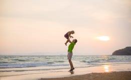 生提起在手上的女儿在日落与yach的海洋海滩 免版税图库摄影