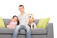 生摆在有女儿和小狗的长沙发 图库摄影