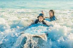 生教他的年轻儿子如何在海冲浪在度假 免版税库存照片
