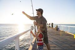 生教的小年轻儿子是渔夫,一起钓鱼在海船坞堤防享用和学会使用鱼r 库存图片
