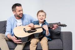 生教他激动的儿子唱歌和使用在吉他 图库摄影