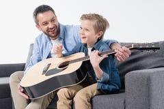 生教他激动的儿子唱歌和使用在吉他 免版税库存照片