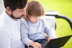 生教他的使用便携式计算机、孩子和技术的女儿 库存照片