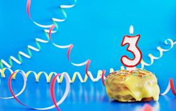 生日三年 与白色灼烧的蜡烛的杯形蛋糕以第3的形式 免版税库存照片