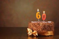 生日与灼烧的蜡烛的巧克力蛋糕作为第六十 库存图片