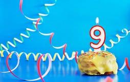 生日九年 与白色灼烧的蜡烛的杯形蛋糕以第9的形式 免版税库存照片