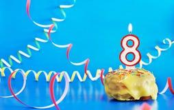 生日八年 与白色灼烧的蜡烛的杯形蛋糕以第8的形式 免版税库存图片