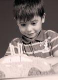 生日吹的男孩蛋糕对光检查愉快的当事人 免版税库存图片
