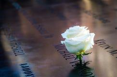 生日在9/11纪念品古铜色栏杆刻记的受害者附近的名字的白色玫瑰在世界贸易中心-纽约,美国 库存图片