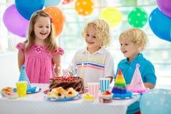 生日开玩笑当事人 吹灭在五颜六色的蛋糕的孩子蜡烛 用彩虹旗子横幅装饰在家,气球 动物农场横向许多sheeeps夏天 库存照片