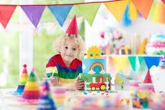 生日开玩笑当事人 吹灭蛋糕蜡烛的孩子 免版税库存照片