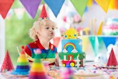 生日开玩笑当事人 吹灭蛋糕蜡烛的孩子 免版税库存图片