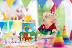 生日开玩笑当事人 吹灭蛋糕蜡烛的孩子 库存图片
