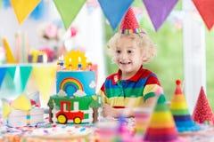 生日开玩笑当事人 吹灭蛋糕蜡烛的孩子 库存照片