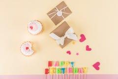 生日快乐字法、信封与丝带和心脏标志顶视图在桃红色 免版税库存图片