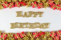 生日快乐金黄文本和金黄和红色礼物在白色 库存照片
