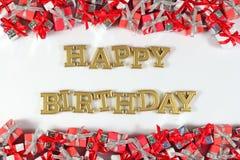 生日快乐金黄文本和银色和红色礼物在白色 免版税库存图片