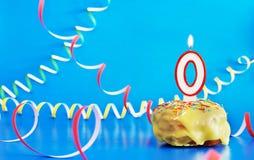 生日新出生 与白色灼烧的蜡烛的杯形蛋糕以第0的形式 免版税库存图片